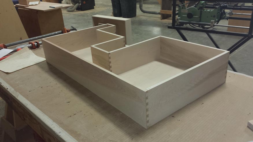 A finished drawer box with custom cutouts.