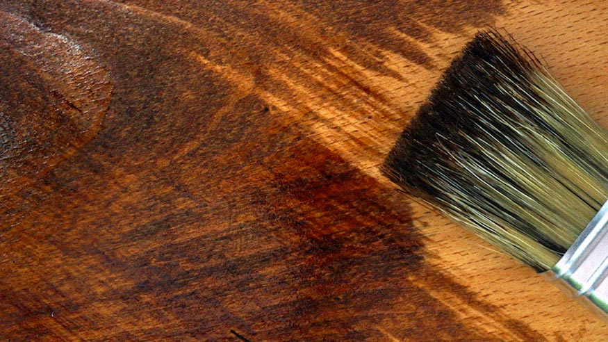 A detail of a brush applying finish to a piece of wood.