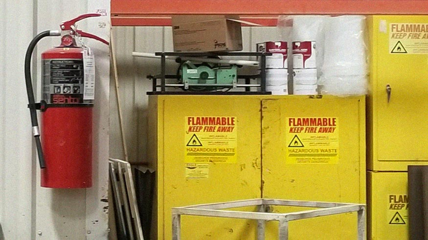 A fire extinguisher posted next to several flame-resistant cabinets.