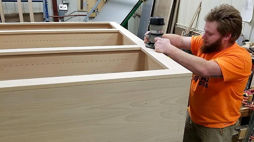 Zach routing the edge of a custom shelving unit.