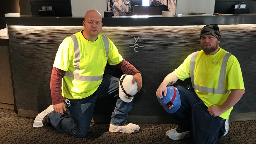 Two of our craftsmen take a knee in front a job well done.